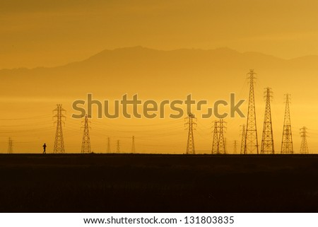 A morning runner runs through a nature preserve in San Francisco Bay Area, California, USA. The power transmission towers and distant mountains formed an impressive backdrop against the morning light. - stock photo