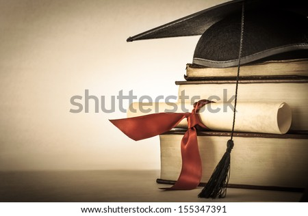 A mortarboard and graduation scroll, tied with red ribbon, on a stack of old battered book with empty space to the left.  Slightly undersaturated with vignette for vintage effect. - stock photo