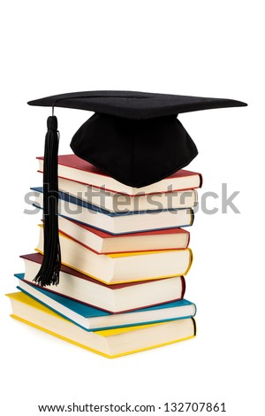 a mortarboard on a pile of books, symbolic photo for education and skills - stock photo