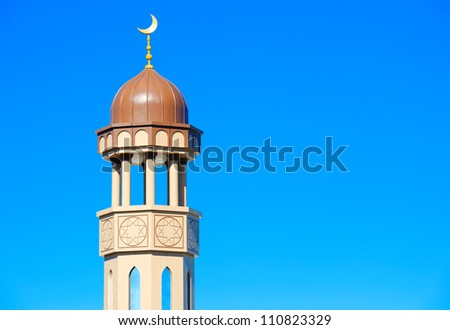 A mosque minaret against clear blue sky (your text on right side) - stock photo