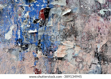 a mostly pink and blue background image of spraypaint and torn posters - stock photo