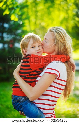 A mother and child at the her hands on green nature background. Childhood and happy family concept - stock photo