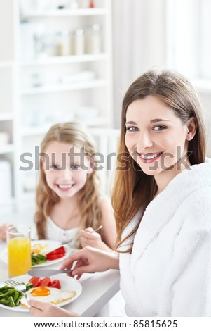 A mother and child have breakfast in the kitchen - stock photo