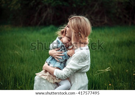 A mother and child in nature. The little girl clung to the mother. The concept of life values, peace, security and love - stock photo