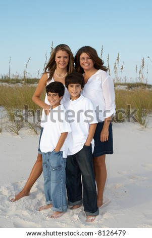 A mother and children standing together on the beach. - stock photo