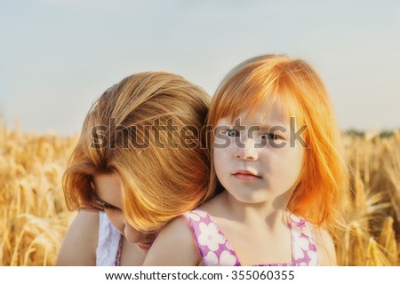 a mother and daughter against the sky and wheat fields