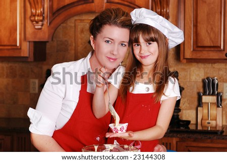 A mother and daughter baking cupcakes together - stock photo