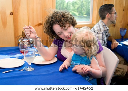 a mother and daughter diner smiling at a restaurant - stock photo
