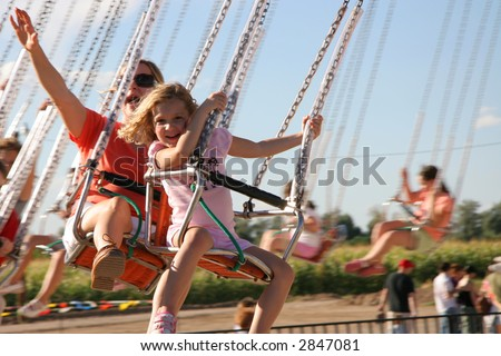 A mother and daughter having fun on amusement park swings. - stock photo