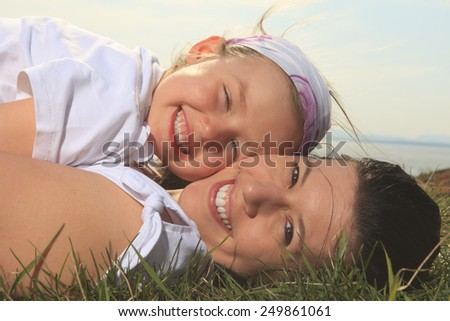 A mother and daughter having fun outside - stock photo