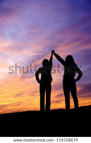 A mother and daughter holding raised hands watch the sunset. - stock photo