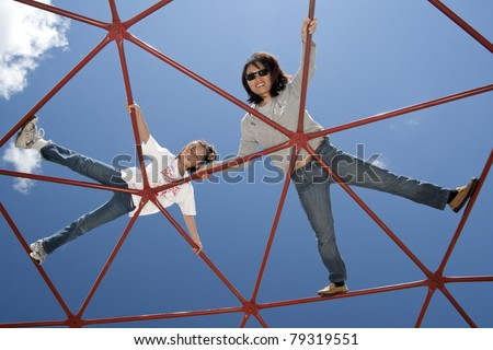 A mother and daughter lay on a jungle jim looking down. - stock photo