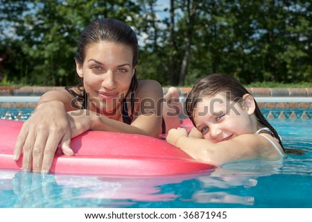A mother and daughter playing in the pool - stock photo