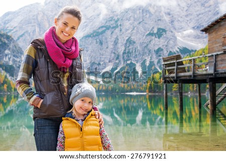 A mother and daughter stand smiling on the shores of Lake Bries. Behind them, the still water provides perfect mirror reflections of the mountains, autumn leaves, and the wooden pier. - stock photo