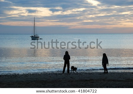 A mother and daughter, walking their dog along a beach at sunrise. - stock photo