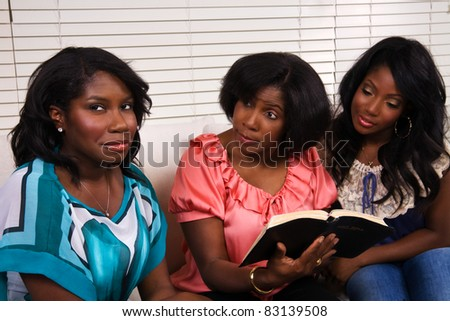 A mother and daughters reading the Bible together, but one daughter does not want to pay attention.