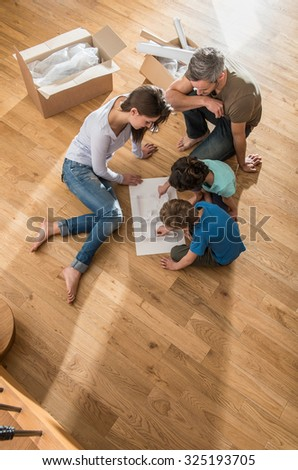 A mother and father are sitting barefoot on the floor of their new house. Their daughter and son are playing with the house model. They are surrounded by open cardboard boxes and palettes. - stock photo