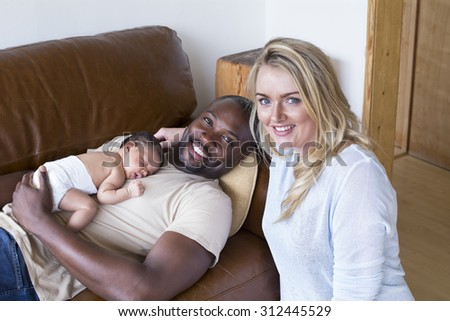 A mother and father with their newborn baby daughter at home. They are looking at the camera and smiling. - stock photo
