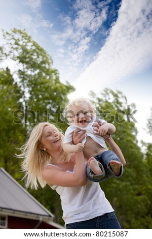 A mother and happy excited son playing together outdoors - stock photo