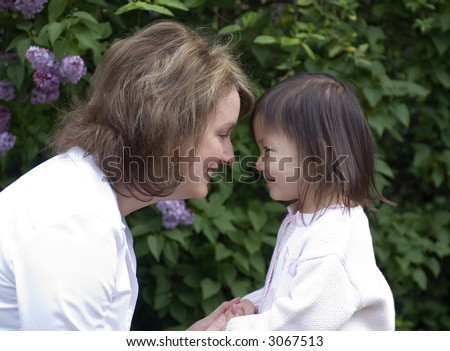 A mother and her adopted girl. Love affection bonding family - stock photo
