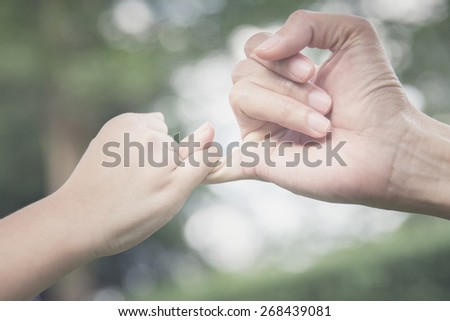 A mother and her child hooking their fingers to make a promise, vintage style - stock photo