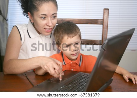 A mother and her child looking at a laptop computer - stock photo