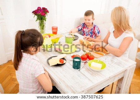 A mother and her children having breakfast at home. - stock photo