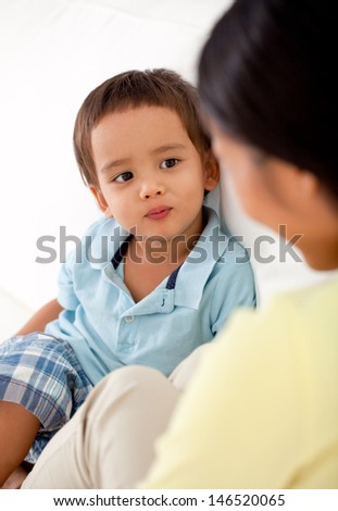 A mother and her cute son looking at each other. - stock photo