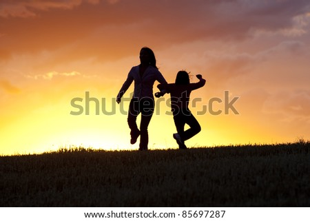 A mother and her daughter do a little dance at sunset. - stock photo