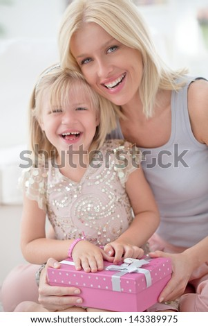 A mother and her daughter sharing happy moments together for the girl's birthday. - stock photo