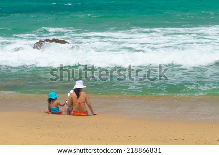 A mother and her daughters are playing on the beach at Phuket, Thailand - stock photo