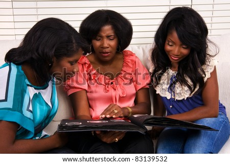 A mother and her daughters look at photos in a family photo album
