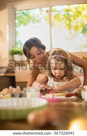 A mother and her four years old blonde daughter are cooking in a luminous kitchen. They are rolling a pasty out on a wooden table full of ingredients. The little girl is focused on her actions. - stock photo