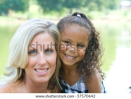 A mother and her mixed race daughter enjoying the park - stock photo