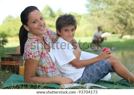 a mother and her son at picnic, the father is fishing - stock photo