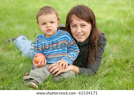 A mother and her son holding an apple are resting on the summer meadow