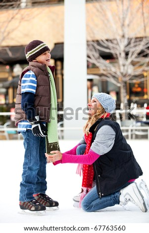 A mother and her son ice-skating - stock photo