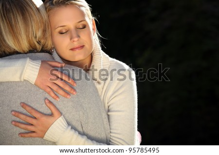 A mother and her teenage daughter hugging. - stock photo