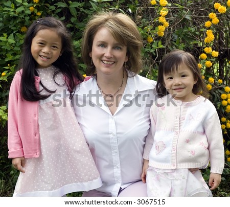 A mother and her two adopted girls. Love affection bonding family - stock photo