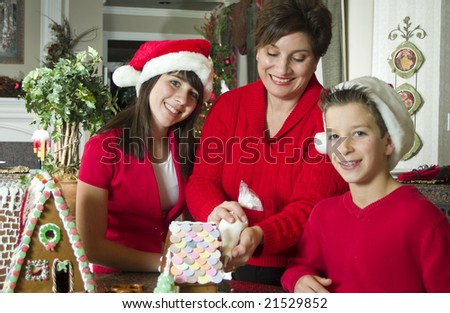 A mother and her two children working together to decorate a gingerbread house.