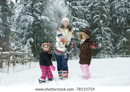 A Mother and her two daughters playing in the snow - stock photo