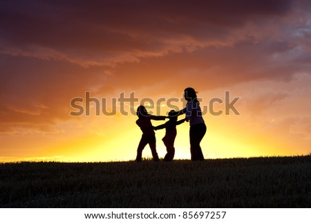 A mother and her two kids play ring around the rosie at sunset. - stock photo