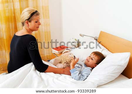 a mother and sick child in bed. influenza. childhood diseases. - stock photo