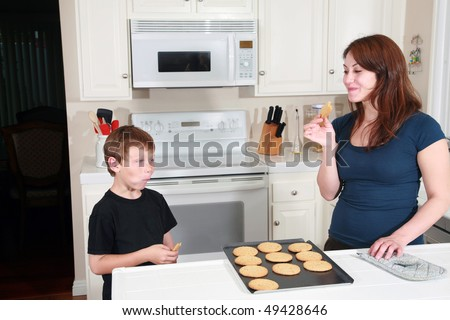 a mother and son enjoy fresh baked peanut butter cookies after school in the kitchen