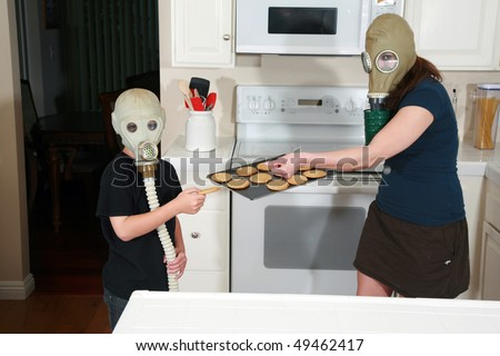 a mother and son enjoy hot fresh baked cookies in their kitchen while wearing gas masks in a post nuclear future - stock photo