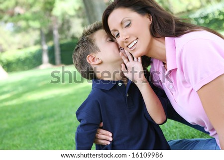 A mother and son having fun while playing in the park - stock photo