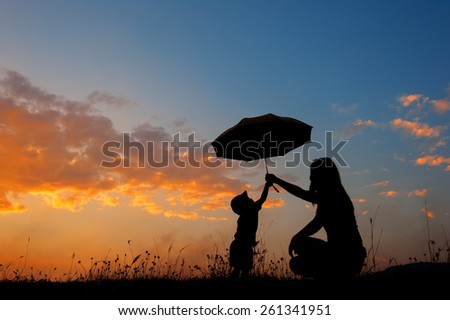 A mother and son holding umbrella and playing outdoors at sunset silhouette - stock photo