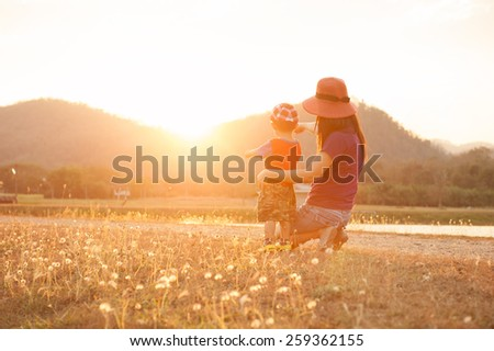 A mother and son playing outdoors at sunset - stock photo