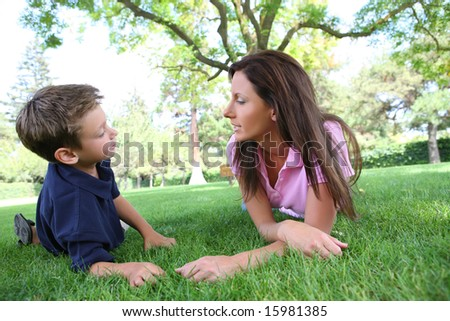 A mother and son talking while relaxing in the park - stock photo