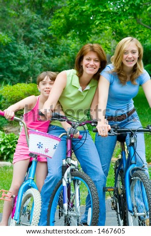 A mother and two daughters clown around on their bicycles for some summer fun. - stock photo